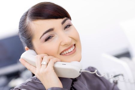 Closeup portrait of happy young businesswoman talking on landline phone in office, smiling. photo