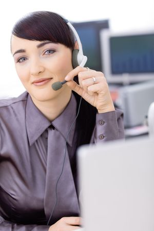Happy young female customer service operator talking on headset, sitting in front of computer screens, smiling. photo