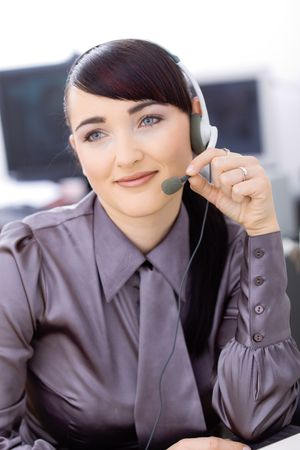 Happy young female customer service operator talking on headset, sitting in front of computer screens, smiling. Stock Photo - 6597218
