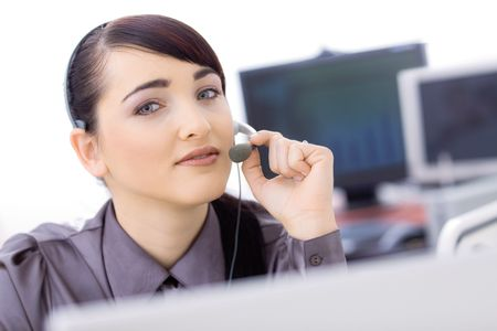 Happy young female customer service operator talking on headset, sitting in front of computer screens, smiling. Stock Photo - 6597202