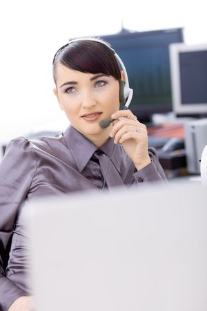 Happy young female customer service operator talking on headset, sitting in front of computer screens, smiling. Stock Photo - 6597217