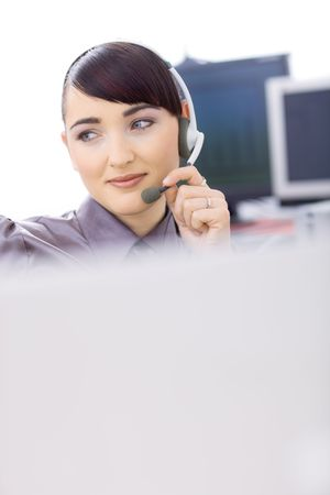 Happy young female customer service operator talking on headset, sitting in front of computer screens, smiling. Copyspace. photo