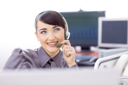 Young female customer service operator talking on headset, holding the microphone, smiling. photo