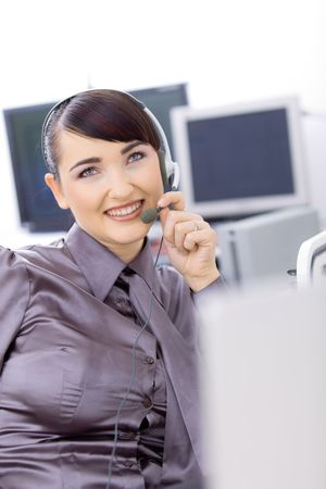 Young female customer service operator talking on headset, holding the microphone. Stock Photo - 6597195