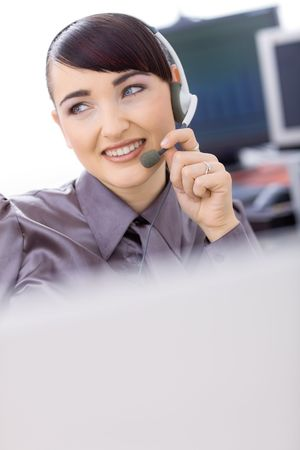 Young female customer service operator talking on headset, holding the microphone. Stock Photo - 6597196