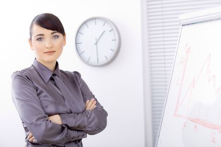 Young businesswomen doing presentation, standing arms crossed in front of whiteboard. photo