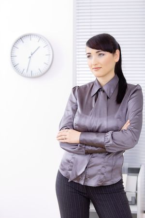 Portrait of young businesswoman standing with arms crossed on office. photo