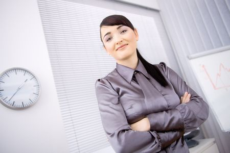 Portrait of young businesswoman standing with arms crossed in office, lloking at camera, smiling. Low-angle shot. photo