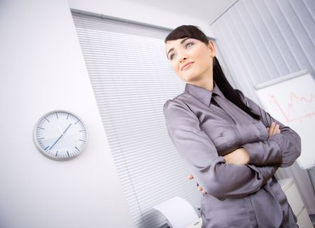 Portrait of young businesswoman standing with arms crossed in office, looking left. Low-angle shot. photo
