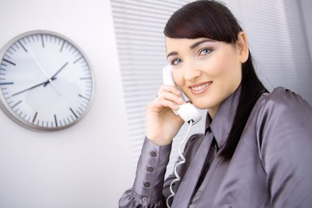 Young businesswoman wearing brown shirt, talking on landline phone in office, smiling. photo