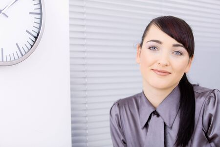 Closeup portrait of attractive young businesswoman, looking at camera, smiling. photo