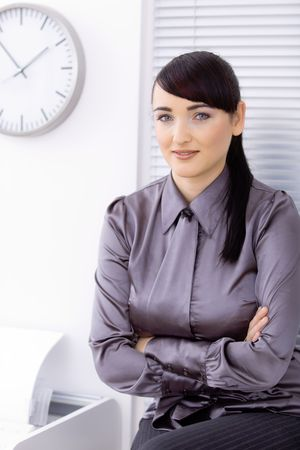 Portrait of a young businesswoman at office, smiling. photo