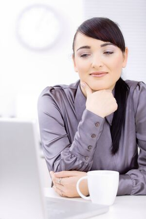 Young businessman sitting at desk at office, thinking, smiling. Stock Photo - 6597235