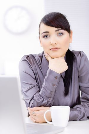 Young businessman sitting at desk at office, thinking. Stock Photo - 6597234