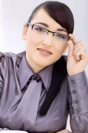 Young happy businesswoman at office, smiling, wearing glasses. photo