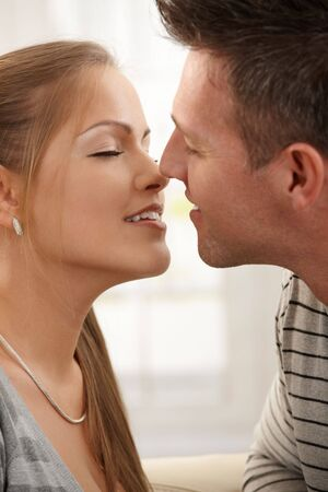 Smiling man kissing woman with eyes closed in closeup. photo