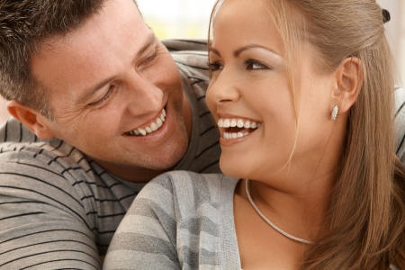 Laughing beautiful couple looking happily at each other in closeup. photo