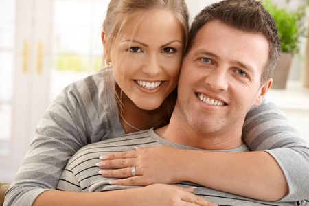 30s thirties: Portrait of happy couple smiling together at home, pretty woman hugging handsome man looking at camera. Stock Photo