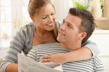 Happy couple sitting at home looking at each other, man holding newspaper, smiling. Stock Photo