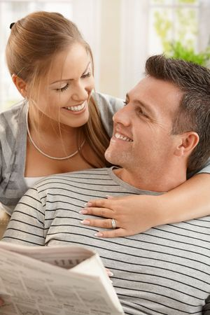 Happy couple sitting at home looking at each other, man holding newspaper, smiling. photo