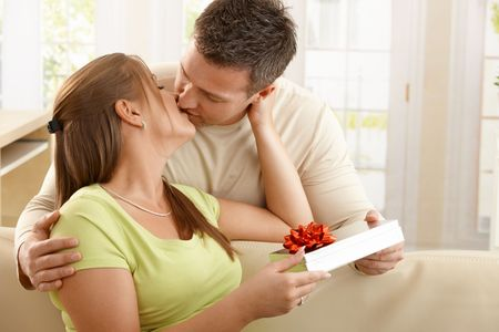 Kissing couple sitting on sofa, man handing present over to woman. photo