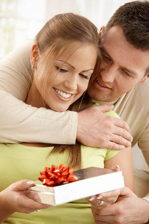 boyfriend: Retrato de la feliz pareja abrazando, mirando hacia abajo en la actualidad en la mano de la mujer, Foto de archivo