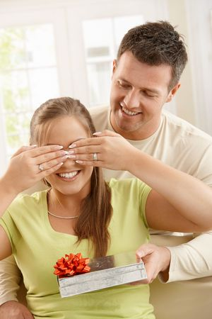 Smiling man giving surprise, smiling woman covering eyes with hands at home. photo