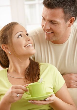 Happy couple sitting in living room, woman holding tea cup with two hands looking up at man smiling. Stock Photo - 6711967