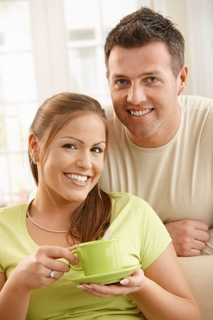 Portrait of smiling couple at home, woman holding tea cup in hands. photo