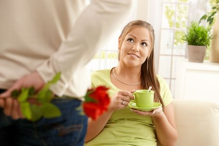 Man bringing flower to woman sitting on couch at home with tea cup, smiling. photo