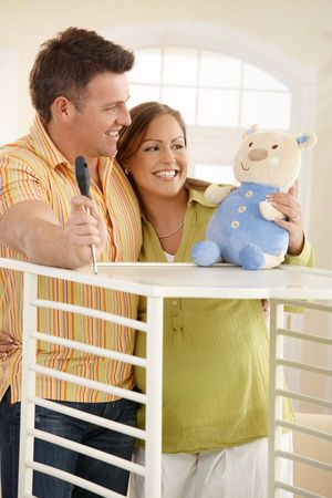 Expectant couple standing together looking at baby toy while putting up baby bed. Stock Photo - 6711691