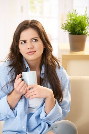 Young woman sitting on sofa at home drinking morning coffee, smiling. photo