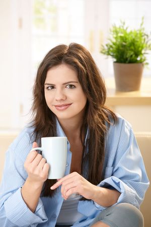 Young woman sitting on sofa at home drinking morning coffee, smiling. Stock Photo - 6711952