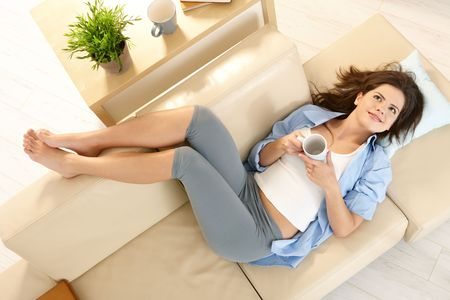 In high angle view girl lying on living room couch with feet up, smiling, holding mug in two hands. photo