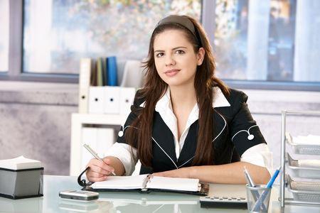 Pretty girl working in office, writing notes into organizer, looking at camera, smiling. Stock Photo - 6711851