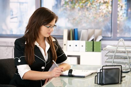 Young woman wearing glasses sitting at office desk, working. photo