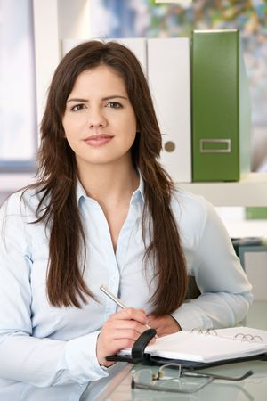 Portrait of young woman looking confidently at camera in office.
