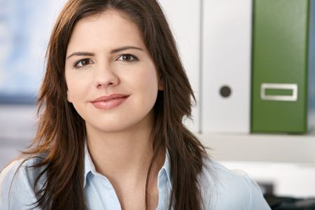 Pretty professional girl smiling at camera, face in closeup, office background. photo