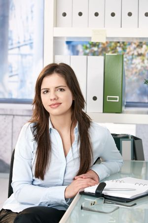 Smart professional woman sitting at office table, looking at camera with small smile. photo