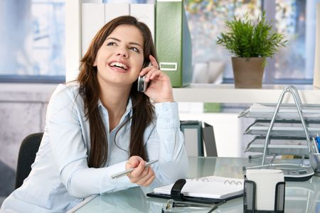 Girl sitting in office speaking on mobile phone, holding pen, laughing. photo