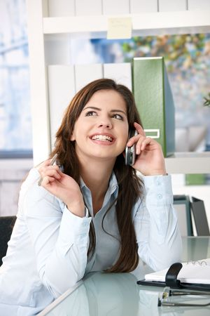 Attractive girl sitting in office looking up, smiling while speaking on mobile phone with pen in hand. photo