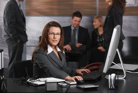 Mid-adult businesswoman dealing with computer tasks sitting at desk in office, looking at camera. photo