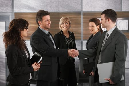 Happy businesspeople shaking hands greeting each other before business meeting in office. photo