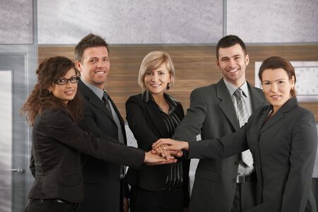 Portrait of happy businesspeople standing in office with joined hands, smiling. photo
