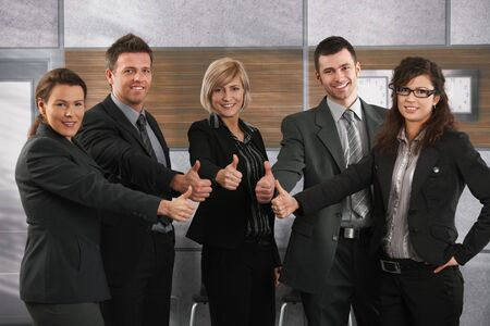 Happy business partners with thumbs up on office corridor, looking at camera, smiling. Stock Photo - 6711499