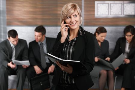 Happy young businesswoman standing in office hallway, holding personal organizer, talking on mobile phone. Stock Photo - 6711847