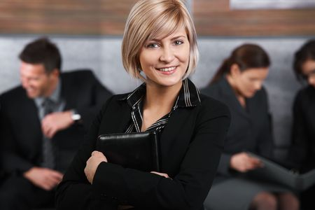 Portrait of mid-adult businesswoman looking at camera, smiling, business people in background. Stock Photo - 6711494