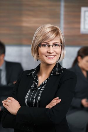 Confident young businesswoman standing in office hallway, arms crossed, smiling. Stock Photo - 6711593