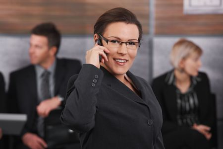 Portrait of happy businesswoman standing in office lobby, talking on mobile phone, smiling. photo