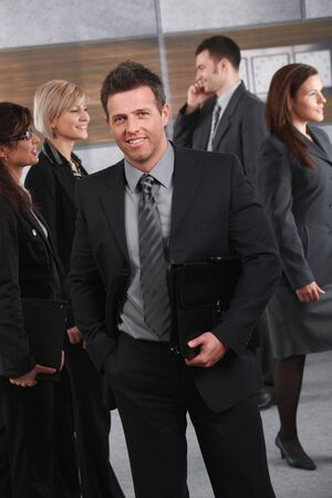 Busy businesspeople walking on office corridor, happy businessman looking at camera. photo